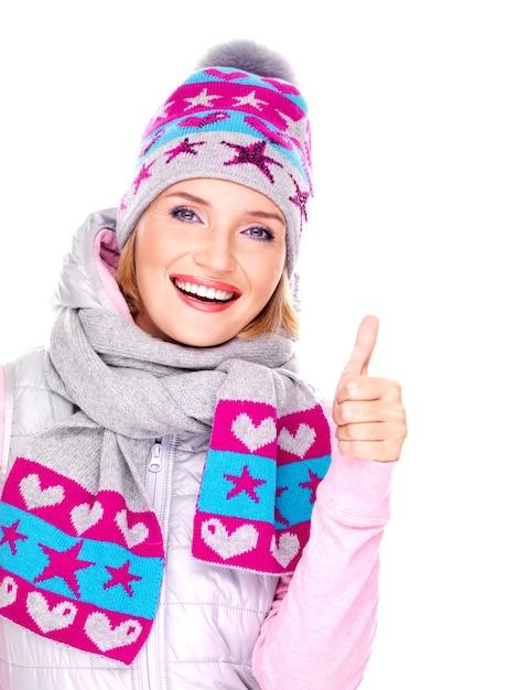 Gelukkig volwassen vrouw in winterkleren met heldere positieve emoties toont duimen omhoog teken geïsoleerd op wit Gratis Foto