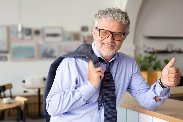 Gelukkig volwassen zakenman permanent in kantoor café, leunend op de toonbank, jas over schouder houden, duim opdagen of iets dergelijks Gratis Foto
