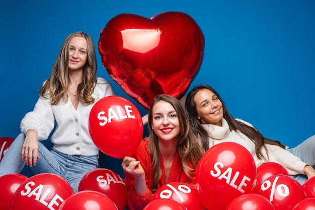 Gelukkig vrij vriendinnen zitten met verkoop rode lucht ballonnen, geïsoleerd op blauwe muur Premium Foto