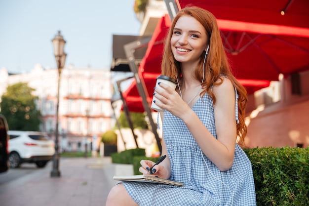 Gelukkig vrolijk roodharigemeisje in oortelefoons Gratis Foto