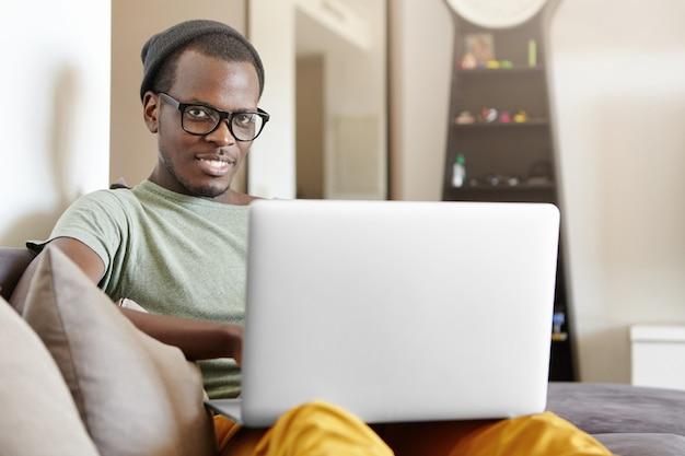 Gelukkig vrolijke jonge donkere man op zoek trendy zittend binnenshuis op grijze bank met laptop pc op schoot, messaging vrienden of kijken naar series online, met behulp van high-speed internetverbinding thuis Gratis Foto