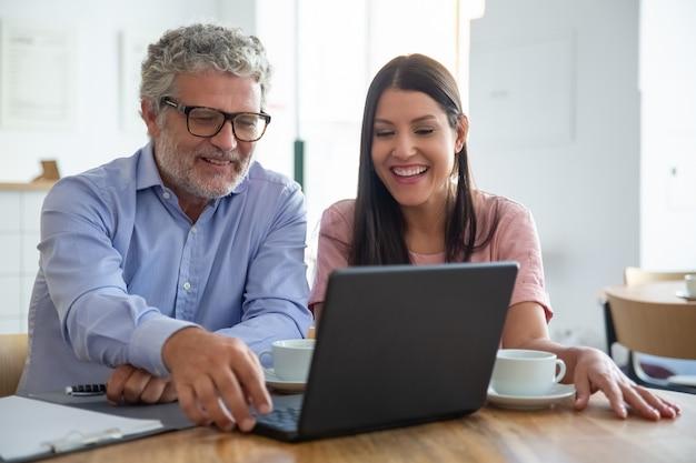 Gelukkig vrolijke volwassen man en jonge vrouw zitten op opengeklapte laptop, kijken naar display, inhoud kijken over kopje koffie en lachen Gratis Foto