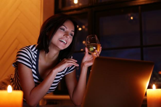 Gelukkig vrouwenportret met glas wijn die het pc-scherm bekijken Gratis Foto