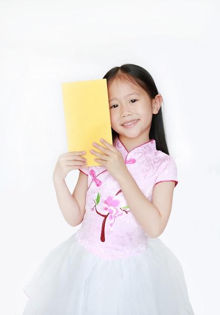 Gelukkig weinig aziatisch kindmeisje die roze traditionele cheongsamkleding dragen die terwijl het ontvangen van het chinese geïsoleerde pakket van de nieuwjaar gouden envelop glimlachen. gelukkig chinees nieuw jaarconcept. Premium Foto
