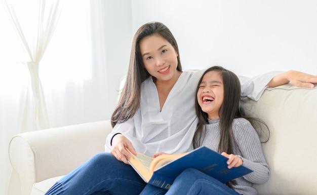Gelukkig weinig aziatisch meisje dat een boek in de woonkamer met haar moeder leest Premium Foto