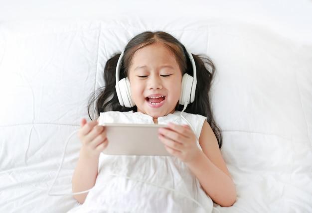 Gelukkig weinig aziatisch meisje dat hoofdtelefoons met behulp van luistert muziek Premium Foto