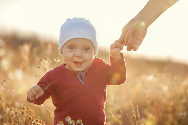 Gelukkig weinig babyjongen die en op een weide op de aard in de zomer zonnige dag zitten glimlachen. Premium Foto