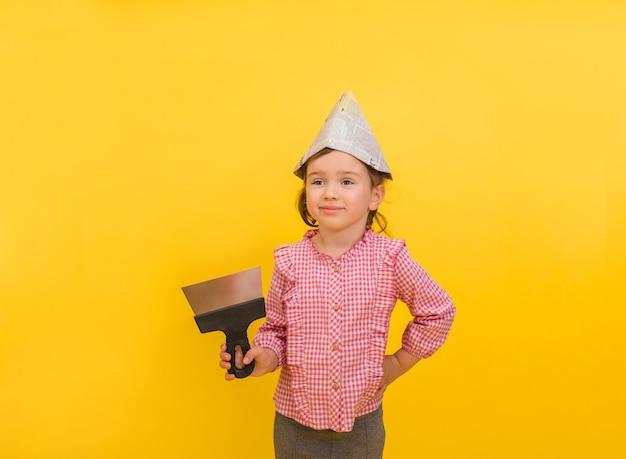 Gelukkig weinig bouwmeisje met een spatel en document krant op geïsoleerd geel Premium Foto