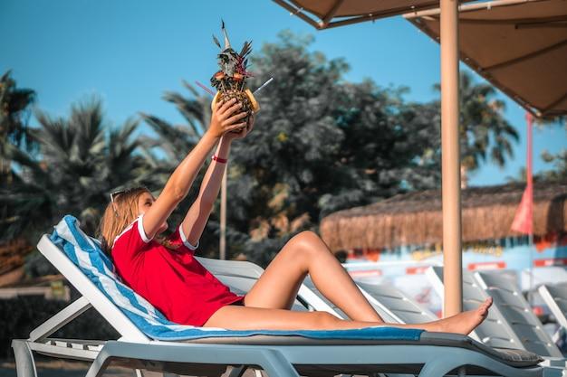 Gelukkig wijfje met ananascocktail die op de ligstoel onder een zonlicht ligt Gratis Foto