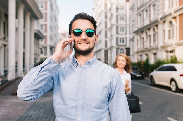 Gelukkig zakenman in zonnebril spreken op telefoon op straat. vrij blond meisje dat hem van achteren betrapt Gratis Foto