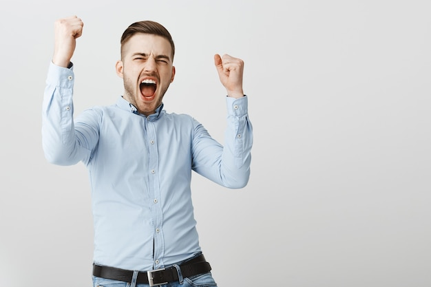 Gelukkig zakenman vuistpomp, ja schreeuwen, prijs winnen, zegevieren over overwinning Gratis Foto