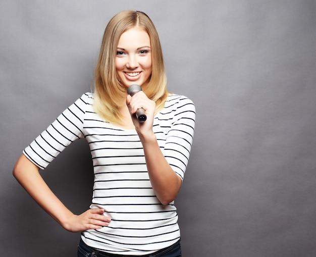 Gelukkig zingend meisje. schoonheid vrouw t-shirt met microfoon op grijs dragen Premium Foto