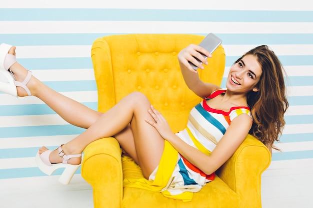 Gelukkig zomertijd van vrolijke stijlvolle ypung vrouw in kleurrijke jurk, met lang brunette krullend haar selfie maken in gele stoel op gestreepte muur. plezier hebben, positieve emoties uiten. Gratis Foto