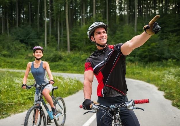 Gelukkig zorgeloos paar rijden op fietsen op de weg. Premium Foto