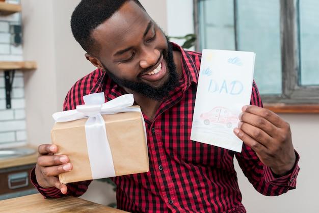 Gelukkig zwarte man met wenskaart en cadeau Gratis Foto