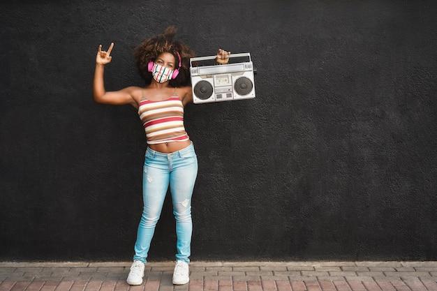 Gelukkig zwarte vrouw met beschermend masker voor het gezicht met plezier en dansen terwijl ze een retro radio vasthoudt - focus op het gezicht Premium Foto