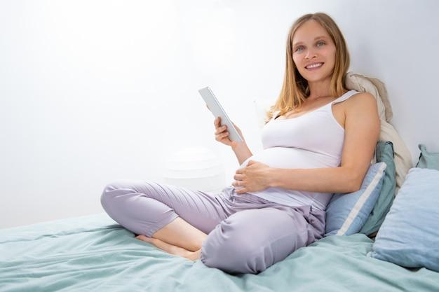 Gelukkige aanstaande moeder met tablet het ontspannen in slaapkamer Gratis Foto