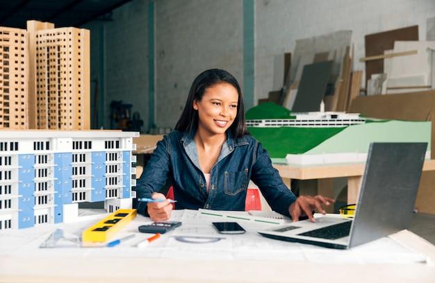 Gelukkige afrikaans-amerikaanse dame met laptop en model van de bouw aan tafel Gratis Foto