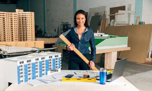 Gelukkige afrikaans-amerikaanse dame met toverstokje dichtbij lijst met laptop en model van de bouw Gratis Foto