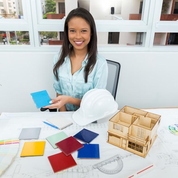 Gelukkige afrikaans-amerikaanse dame op stoel die voorgevelpaneel dichtbij plan en model van huis op lijst tonen Gratis Foto