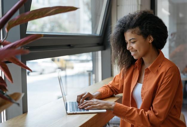 Gelukkige afrikaanse amerikaanse vrouwenschrijver die freelance project van huis werken. zakenvrouw met behulp van laptop, informatie zoeken op website. succesvol bedrijf. online trainingen concept Premium Foto