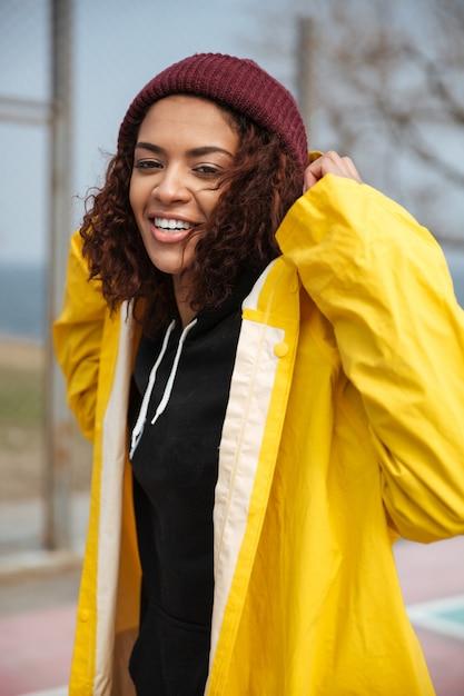 Gelukkige afrikaanse krullende jonge dame die gele laag draagt die in openlucht loopt Gratis Foto