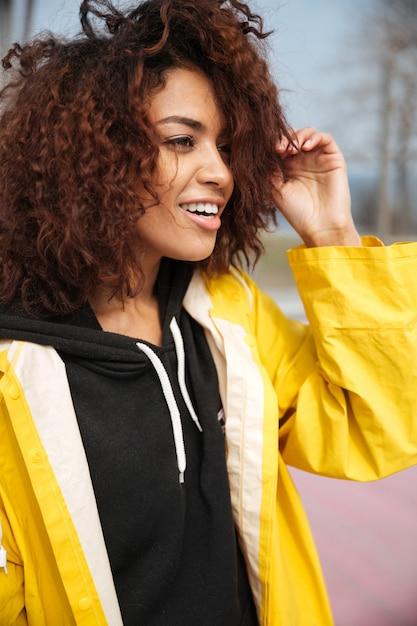 Gelukkige afrikaanse krullende jonge vrouw die gele laag draagt Gratis Foto