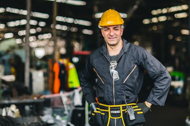 Gelukkige arbeider, de knappe arbeid van de portretglimlach met de riem van veiligheidspakhulpmiddelen en de radiodienstmens in fabriek. Premium Foto