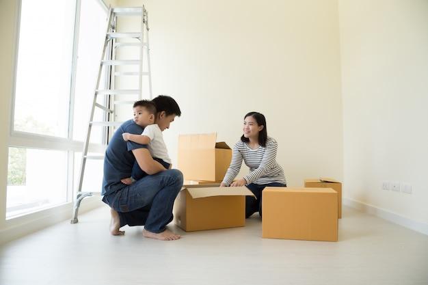 Gelukkige aziatische familie met kartonnen dozen in nieuw huis op bewegende dag Premium Foto