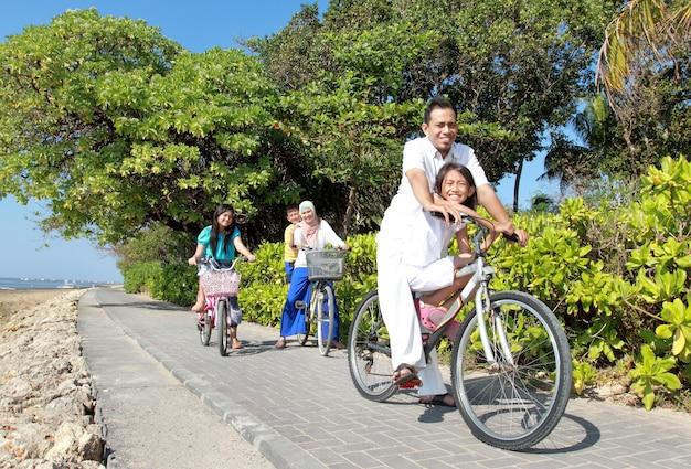 Gelukkige aziatische familie paardrijden fietsen in de mooie ochtend op het strand Premium Foto