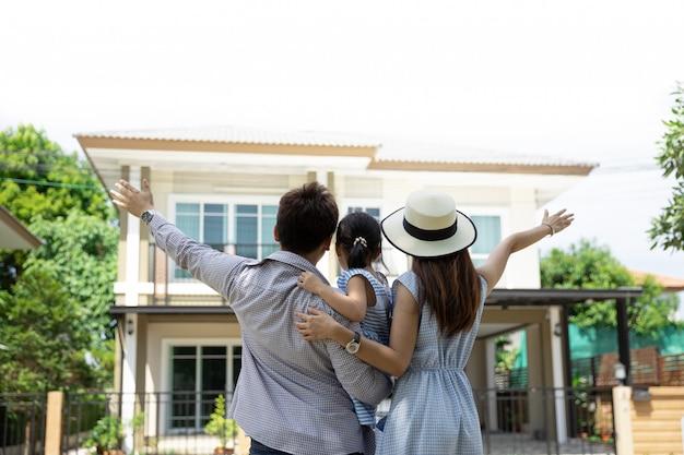 Gelukkige aziatische familie. vader, moeder en dochter dichtbij nieuw huis. onroerend goed Premium Foto