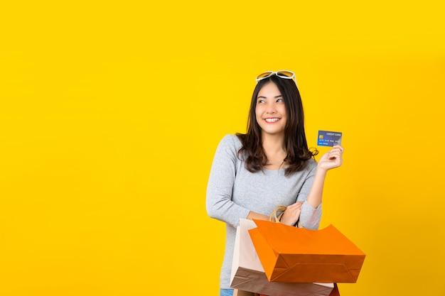 Gelukkige aziatische glimlachende vrouw die creditcard gebruikt en een het winkelen coloful zak draagt voor het voorstellen van online het winkelen op geïsoleerde gele muur, exemplaarruimte en studio, de zwarte verkoop van het vrijdagseizoen Premium Foto