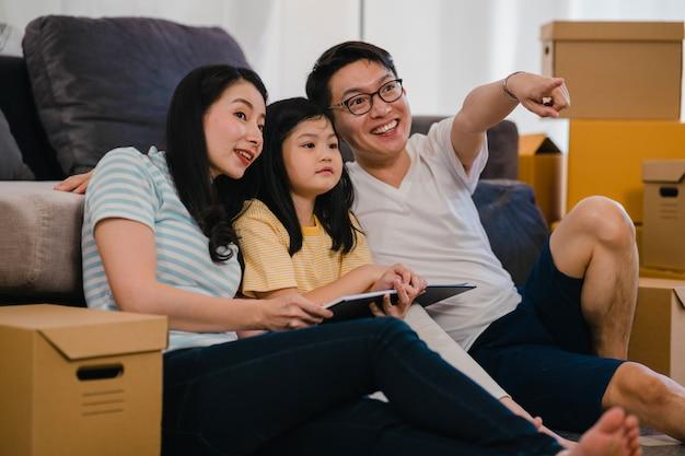 Gelukkige aziatische jonge familiehuiseigenaren kochten nieuw huis. chinese moeder, vader en dochter omhelzen elkaar en kijken uit naar de toekomst in een nieuw huis nadat ze samen in verhuizing op de vloer met dozen zijn verhuisd. Gratis Foto