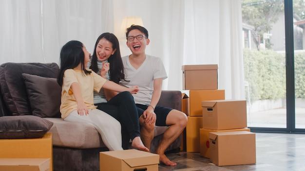 Gelukkige aziatische jonge familiehuiseigenaren kochten nieuw huis. japanse moeder, vader en dochter omhelzen elkaar en kijken uit naar de toekomst in een nieuw huis nadat ze samen in verhuizing op de bank met dozen zijn gaan zitten. Gratis Foto
