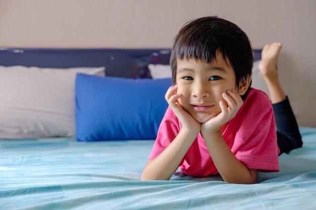 Gelukkige aziatische jongenshand aan wang op blauw bed Premium Foto