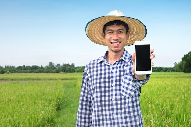 Gelukkige aziatische landbouwersmens die smartphone gebruiken die camera kijken. havest rijst boerderij met technologie Premium Foto