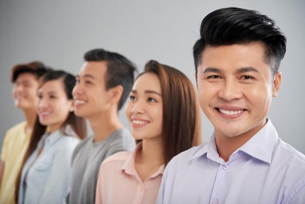 Gelukkige aziatische mens die camera bekijken die zich op de voorgrond van zijn collega's bevinden Gratis Foto