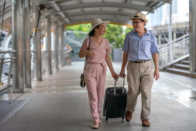 Gelukkige aziatische paar hogere toeristen die kofferhandvat in de stad houden terwijl het reizen Premium Foto