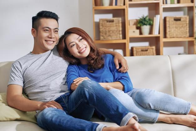 Gelukkige aziatische paar thuis op bank zitten samen, weg kijkend en glimlachend Gratis Foto