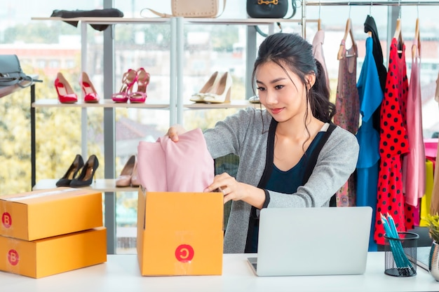 Gelukkige aziatische toevallige dame werkende start kleine bedrijfsondernemer kmo in klerenwinkel. Premium Foto