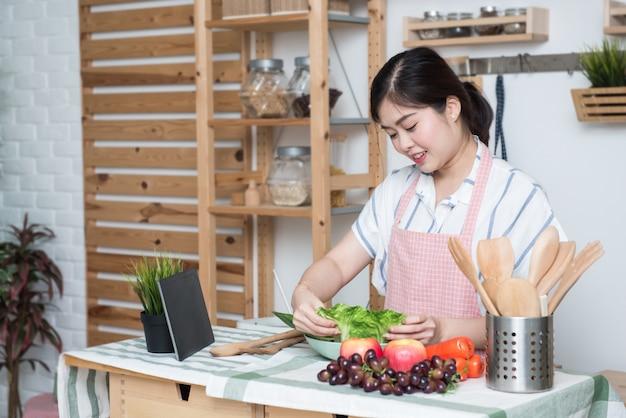 Gelukkige aziatische vrouw die de keukenlezing van de receptentablet thuis het koken kijken Premium Foto