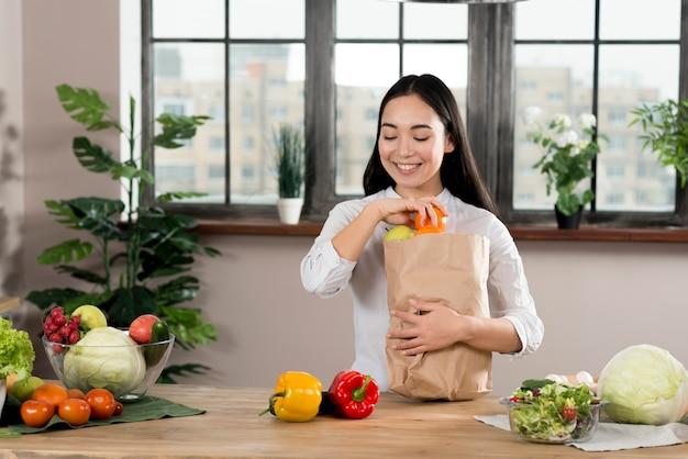 Gelukkige aziatische vrouw die groenten verwijderen uit kruidenierswinkelzak op houten keukenteller Gratis Foto