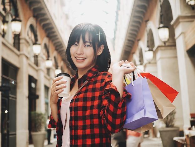 Gelukkige aziatische vrouw met boodschappentas. Premium Foto