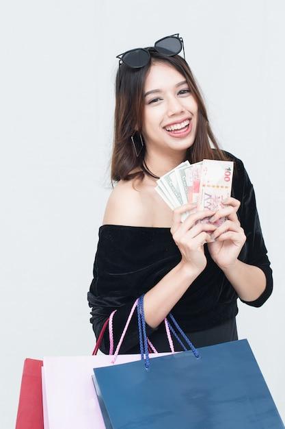 Gelukkige aziatische vrouwen met het winkelen zak en het houden van geld Premium Foto