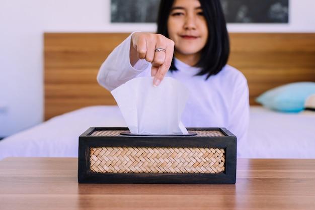 Gelukkige aziatische vrouwenhanden die wit papieren zakdoekje van houten vakje trekken Premium Foto