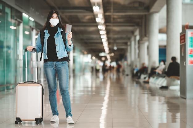 Gelukkige aziatische vrouwentoerist die de holdingspaspoort van het gezichtsmasker dragen Premium Foto