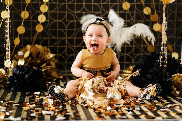 Gelukkige baby die cake op haar eerste verjaardagspartij eet. cakesmash voor een klein meisje Gratis Foto