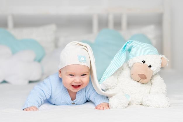 Gelukkige baby op het bed in een kap. textiel en beddengoed voor kinderen. pasgeboren baby met een stuk speelgoed beer Premium Foto