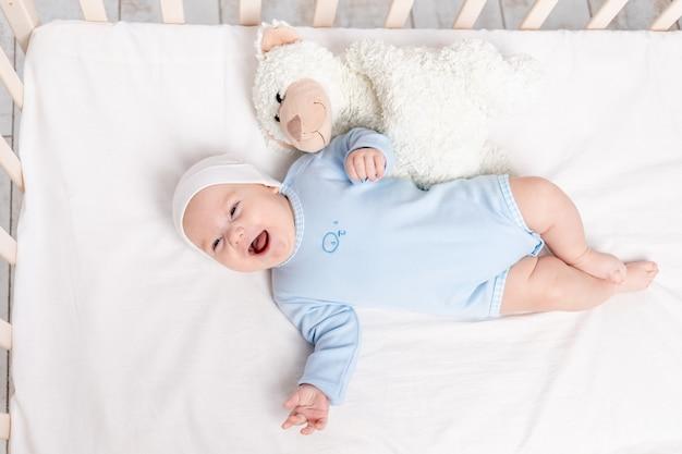 Gelukkige babyjongen in voederbak met teddybeerstuk speelgoed, kinderen en geboorteconcept Premium Foto