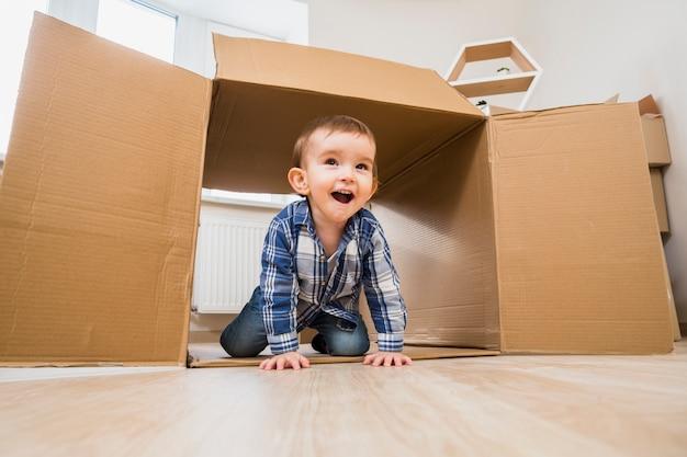 Gelukkige babypeuter die binnen een open kartondoos thuis kruipen Gratis Foto